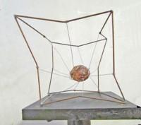 cuore anatomico in resina sospeso all'interno di uno scheletro di un cubo in rame piegato in modo tale da simboleggiare le compenetrazioni tra l'ambiente circostante e l'essenza dell'uomo